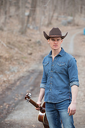 cowboy with a guitar in a rustic setting