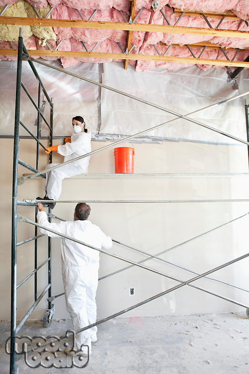 Two construction workers painting a room