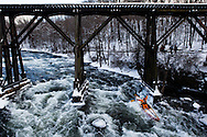 Harry Wallace celebrates while passing underneath the railroad trestle across the Winnipesaukee River in Franklin during the annual First Day Kayak Run on Wednesday, January 1, 2014. Roughly 40 paddlers from the Merrimack Valley Paddlers and other New England outdoor associations battled class III and IV rapids while braving temperatures in the teens.<br /> <br /> (WILL PARSON / Monitor staff)