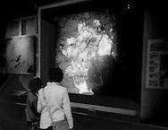 Mother and son looking at an interactive map where buttons are pushed, lighting up neighborhoods in Tokyo on the date they were bombed during WWII/Pacific War, which is factually accurate but this permanent exhibit at Tokyo's Edo* Museum, with no meaningful context offered about the bigger war, leaves the museum visitor impression that Japan was the sole, innocent victim of that massive war.<br /> *(Edo is the old name for Tokyo before it became the &quot;East Capital&quot; [東京] of Japan.)