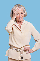 Senior woman in casuals suffering from headache against blue background