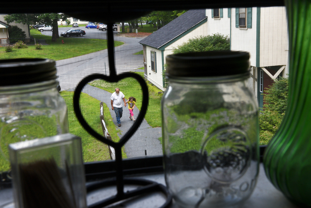Savannah Triplett, 6, shadows her grandfather Mike Lesperance, of Bradford, left, as he makes trips from Savannah's father's Pine Tree Lane apartment to a moving van Thursday, June 25, 2015. After living with the burden of high child care costs and low wage work so that Savannah could be near her mother's family in Vermont, Mike Triplett moved the following day with his daughter to live with his family in Virginia. (Valley News - James M. Patterson)<br />