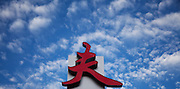A red Chinese character, or hanzi, above a farmers market in Flushing, Queens in a sky of white fluffy altocumulus clouds.