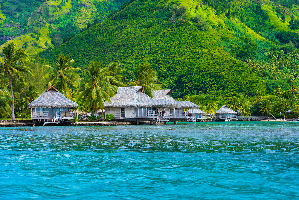 Thatched roof houses on a lagoon in the South Pacific at the foot of a mountain.