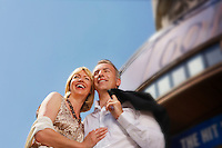 Well dressed smiling couple standing by building outdoors low angle view