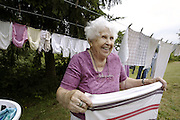 071707-  Upper Green Valley- ..?You haven't lived until you have dried your clothes outside,? says Grayce Fremouw, 87, (CQ) as she stretches out a dishtowel while folding her clothes that had dried on her clothesline outside her home July 17, 2007 off South East Green Valley Road. Fremouw said she one of those people who prefers air-drying her clothing. ?I love hanging my clothes out here,? Fremouw said. ?They smell so clean and remind me of the outdoors.? Fremouw has lived in the valley since 1962 and has had her families last name added to the Upper Green River Valley sign that use to be posted at west entrance of the valley in the 1960s. Fremouw is also a member of The Green Valley Neighbors women's club.