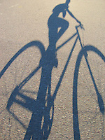 The shadow of a mountain bike on gray pavement.