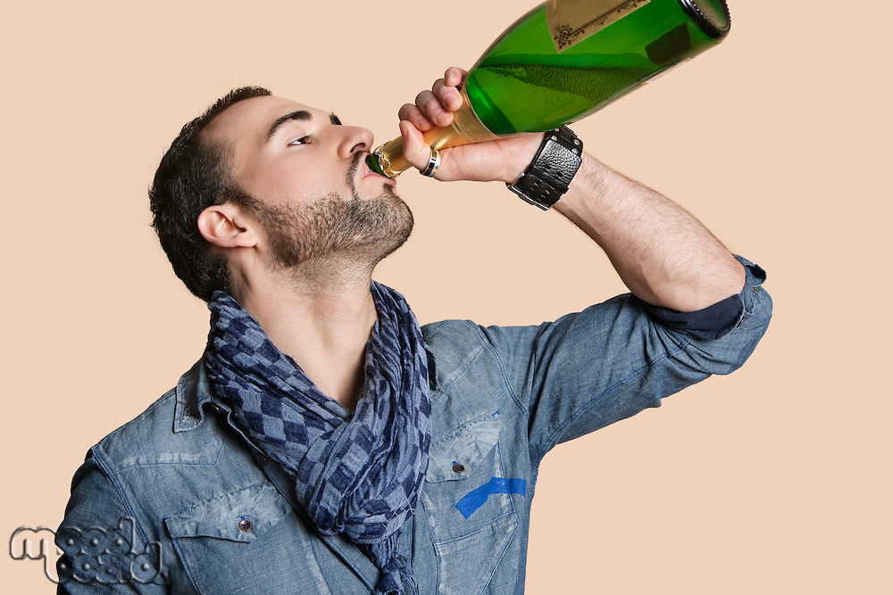 Young man drinking champagne from bottle over colored background