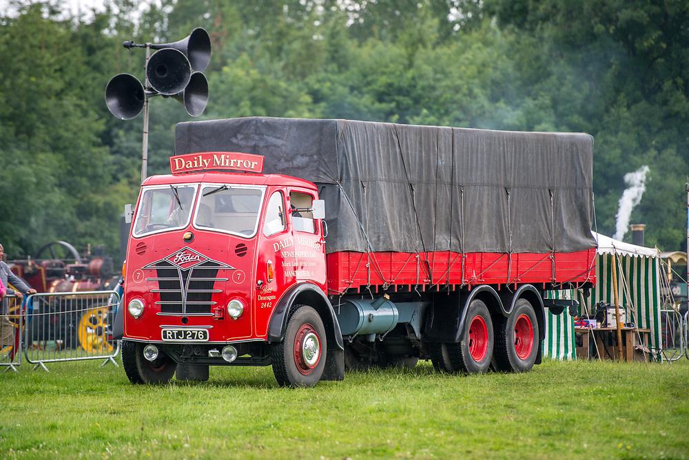 Vintage red newspaper delivery truck sits parked in grass, Masham, North Yorkshire, UK