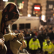 A journalist from Press TV working her mobile phone. The London Stock Exchange was attempted occypied in solidarity with Occupy Wall in Street in New York and in protest againts the economic climate, blamed by many on the banks. Police managed to keep people away fro the Patornoster Sqaure and the Stcok Exchange and thousands of protestors stayid in St. Paul's Square, outside St Paul's Cathedral. Many camped getting ready to spend the night in the square.