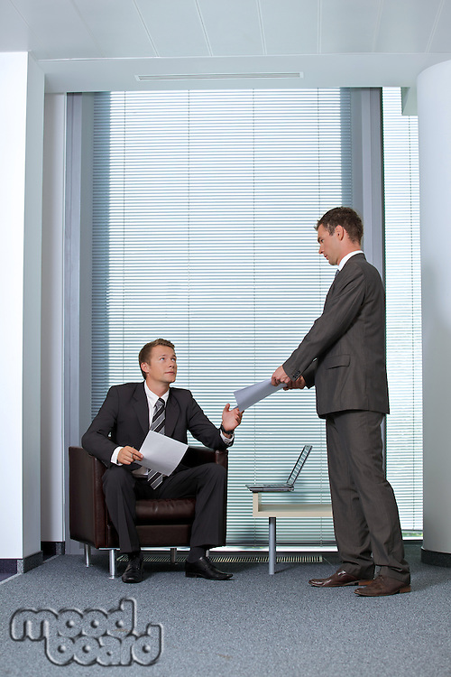Businessman giving paper to colleague in office