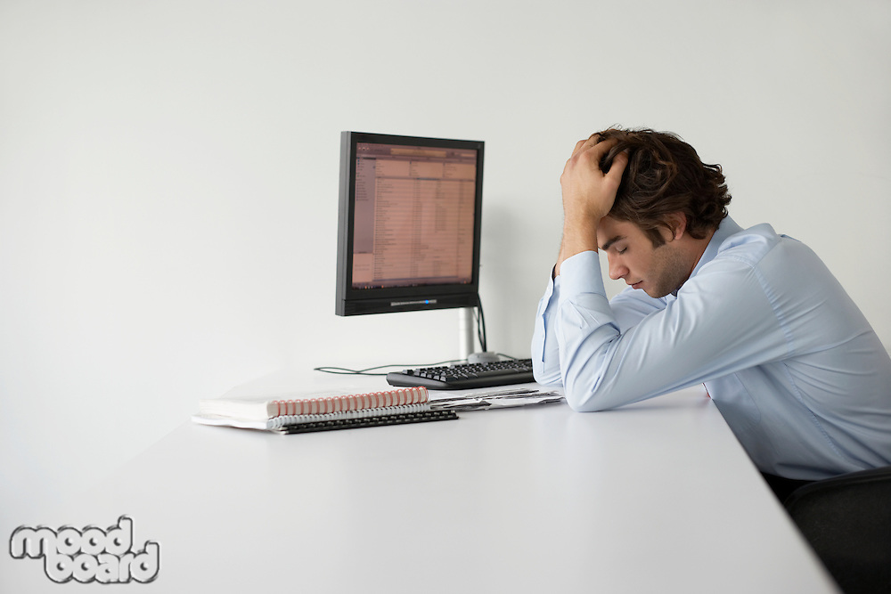 Business man with head in hands sitting at office desk side view