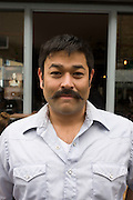 Young man in his thirties street portrait with moustache.