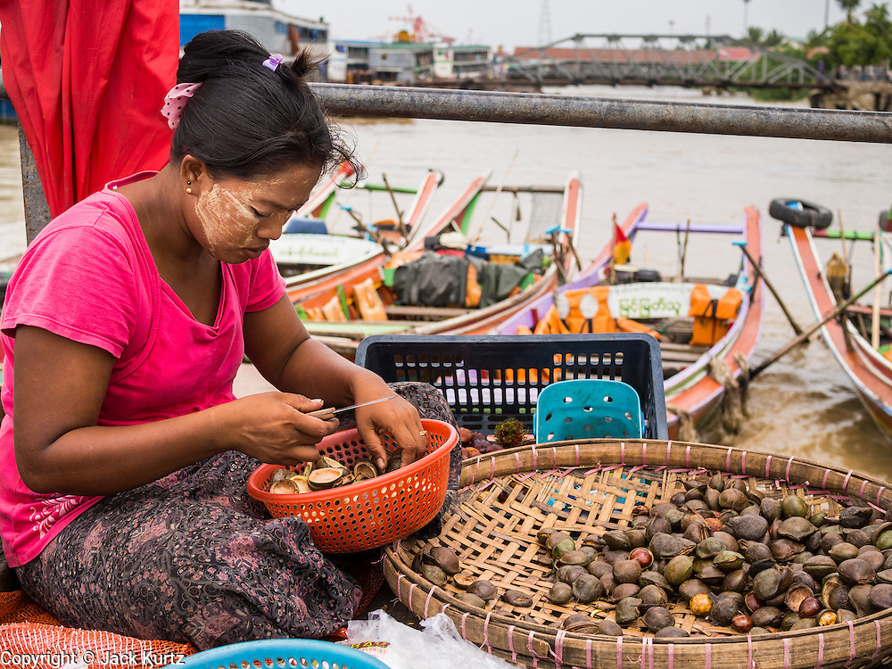 08 JUNE 2014 - YANGON, MYANMAR: A vendor on a pier on the Yangon waterfront. Yangon, Myanmar (Rangoon, Burma). Yangon, with a population of over five million, continues to be the country's largest city and the most important commercial center.      PHOTO BY JACK KURTZ