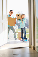 Happy father and son with cardboard boxes entering into new house