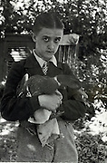 young boy standing holding his pet duck