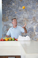 Mature man throwing orange into air standing at kitchen countertop