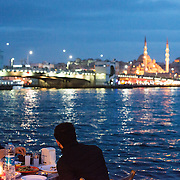 Diners eat at popup outdoor restaurants on the banks of the Golden Horn in Karakoy, with the Galata Bridge and New Mosque in the background.