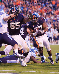 "Virginia guard B.J. Cabbell (65) delivers a key block for Virginia running back Cedric Peerman (37) to set up the game tying touchdown late in the fourth quarter.  The Virginia Cavaliers defeated the #18 ranked North Carolina Tar Heels 16-13 in overtime in NCAA football at Scott Stadium on the Grounds of the University of Virginia in Charlottesville, VA on October 18, 2008.  The 113th meeting of the two teams, dubbed the ""Oldest Rivalry in the South"", saw UVA continue its streak of consecutive home victories over UNC -- the last time the Tar Heels won in Charlottesville was 1981."