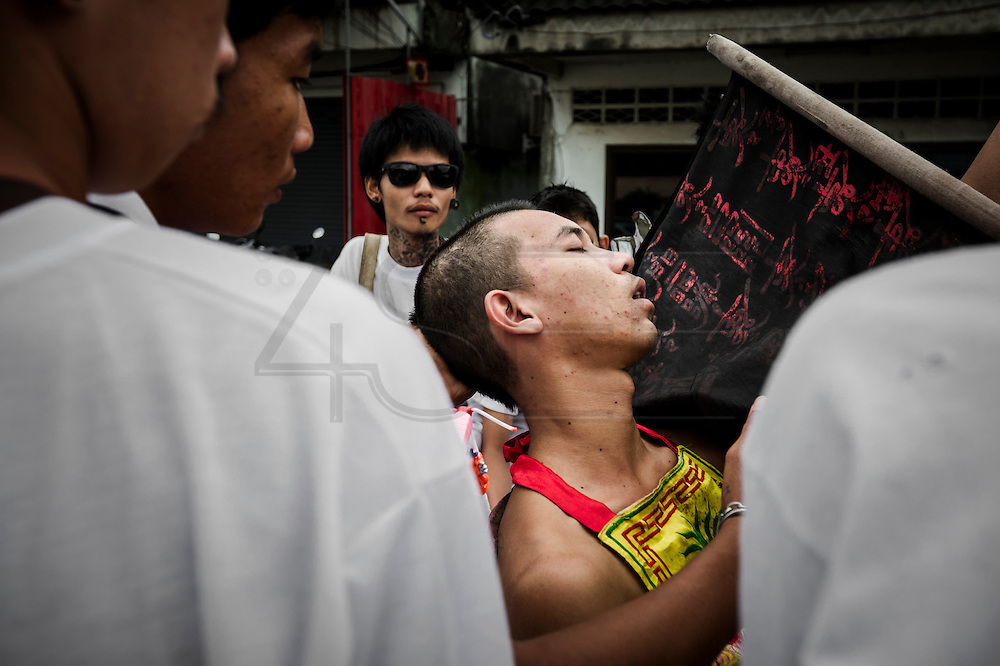 A warrior passes out during street procession near Phuket town. Every year during the ninth lunar month of the Chinese calendar, the Phuket Vegetarian Festival kicks off. The religious festival in Phuket, Thailand, lasts for 10 days, during which sacred rituals take place in the many Chinese shrines and temples. Walking on fire and climbing ladders with bladed rungs barefoot are two of several rituals believed to bring good fortune. The main purpose of the festival, however, is spiritual cleansing and merit-making.<br />