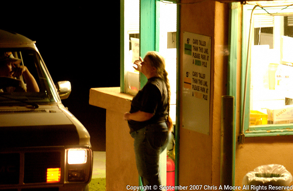 Driver discusses ticket pricing with attendent at the ticket booth.