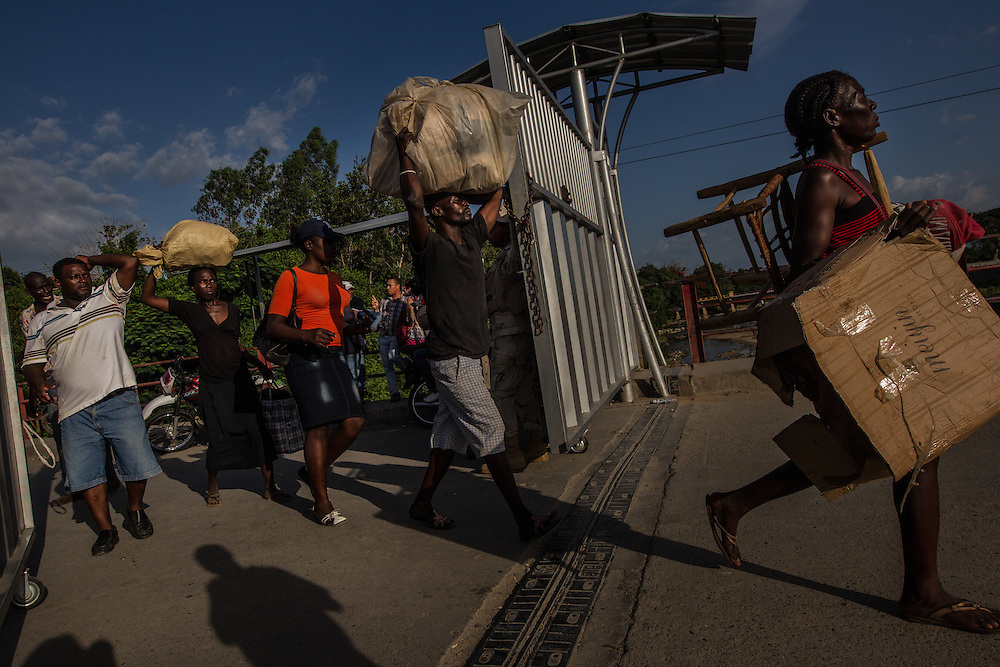 DAJABÓN, DOMINICAN REPUBLIC - JUNE 26, 2015: A Dominican man (left) shouts at Haitians that had crossed into the binational frontier market zone to work for the day as they cross through the border gate that separates the Dominican Republic from Haiti.  Twice a week, the border is opened up so that people can pass freely to buy and sell in the market without registering with border officials. PHOTO: Meridith Kohut for The New York Times