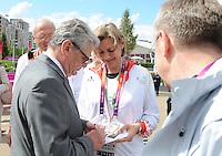 Olympia 2012 London   28.07.2012 Bundespraesident Joachim Gauck (l.) gibt bei einem Besuch im Olympischen Dorf ein Autogramm.
