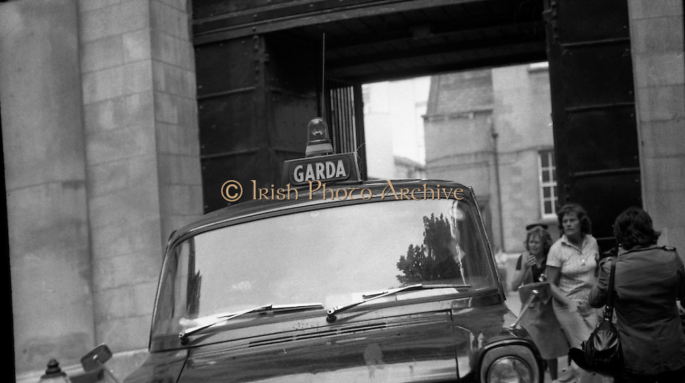 Fergus Rowan sits in at Bank of Ireland.  (J70)..1975..22.08.1975..08.22.1975..22nd August 1975..As a result of the 1970 bank strike which lasted for six months, the Rowan family business found itself in financial difficulties. During the strike the Rowans had had to accept cheques in good faith in order to stay in business. When the cheques came for settlement the bank refused as they stated that some were 'dodgy'. This put severe strain on the business which was eventually put into receivership.As part of the process the Rowan business beside the bank was put up for sale and was purchased by B.o I. Rowan was outraged and started a campaign against the bank which culminated in a sit in at the banks headquarters in Westmoreland St,Dublin. He also became a thorn in the side of the bank at the A.G.Ms raising many points...Picture shows the Garda van, containing Mr Rowan, being followed by his daughter ,Julie, and by Mr Rowan's sister as it leaves the back of the bank after his removal from the premises.
