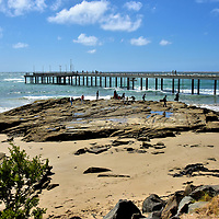 Lorne Pier in Lorne on Great Ocean Road, Australia<br /> Lorne Pier jets out into Louttit Bay, named after Captain Louttit. His schooner Will Watch was forced into these waters during a huge storm in 1841. Eight years later, the first settler arrived. The logger William Lindsay called the surrounding area Louttit Bay until the township was renamed Lorne in 1871. As the timber industry grew, a pier was built in 1879 to accommodate ships. Soon cranes were added to service an influx of fishing boats. Much of that activity has dissipated. But you can hook salmon, barracuda and squid by tossing a line off this pier built in 2007. Or if you want a guaranteed fresh catch, order seafood at the Lorne Pier Restaurant.