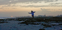 26 December 2015. Grand Isle, Louisiana.<br /> Boxing Day on the beach. Leaping for joy on the beach on an unseasonably warm evening in December.<br /> Photo©; Charlie Varley/varleypix.com