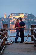 A couple at the end of a dock look out upon Isola San Giulio from the town of Orta San Giulio on Lake Orta, Piedmont, Italy.