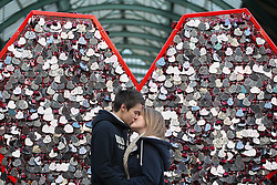 © licensed to London News Pictures. London, UK 14/02/2013. James Baker and Taryn Greaves kissing in front of a heart-shaped fence where couples put their to heart-shaped name tags to mark Valentine's Day in Covent Garden, London. Photo credit: Tolga Akmen/LNP