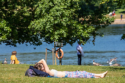 © Licensed to London News Pictures. 19/05/2020. London, UK. A women sunbaths next to the Serpentine in the warm sunshine in Hyde Park as weather experts predict a high of 27c this week. Last week the Government eased the law on lockdown to let people spend more time outside. Photo credit: Alex Lentati/LNP