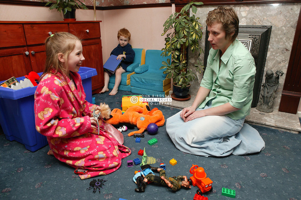 Single parent trying to get her children to tidy up their toys before they go to bed,