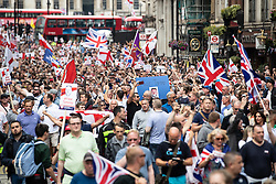 © Licensed to London News Pictures. 09/06/2018. London, UK. 1000s of supporters of EDL founder Tommy Robinson ( real name Stephen Yaxley-Lennon ) march down Whitehall to a demonstration in Westminster after Robinson was convicted of Contempt of Court . Robinson was already serving a suspended sentence for Contempt of Court over a similar incident , when he was convicted on Friday 25th May 2018 . Photo credit: Joel Goodman/LNP