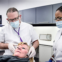 Nederland, Kerkrade, 10 maart 2016.<br /> Een tandarts-gnatholoog behandelt patiënten met klachten in het kauwstelsel. <br /> Op de foto: tandarts-gnatholoog Jan Thijssen luistert door een stethoscoop in het oor naar het kaakgewricht van een patient<br /> <br /> Foto: Jean-Pierre Jans