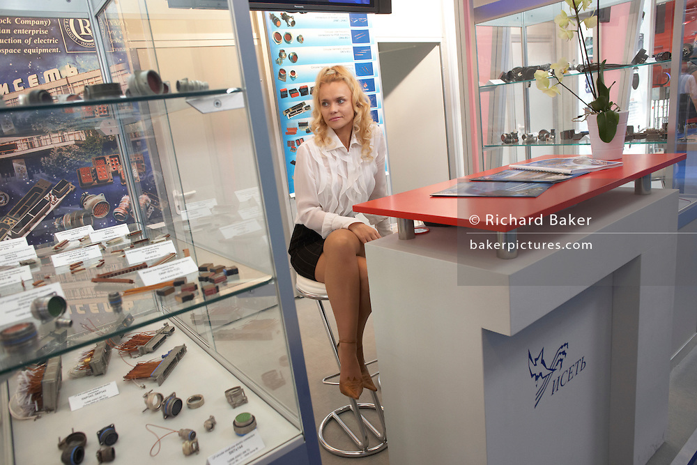 A short-skirted Russian lady perches on a stool during the Paris Air Show exhibition at Le Bourget airfield