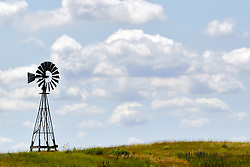 Old west style windmill dots the landscape standing as a landmark against the prairie horizon in Northwest Nebraska