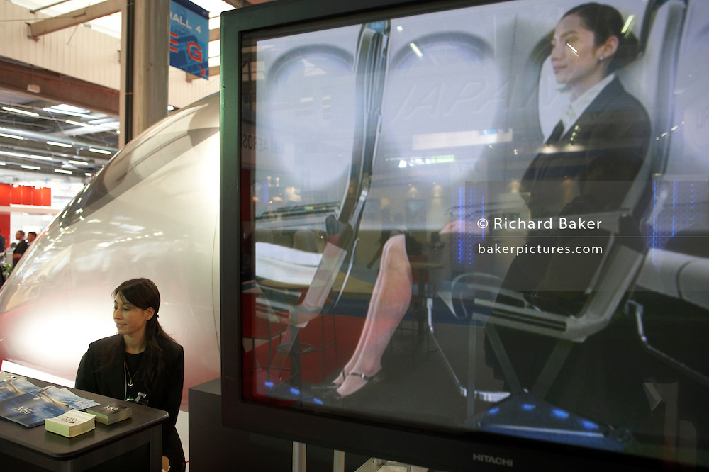 Japanese lady delegate sits outside full-size mock-up the Mitsubishi Regional Jet (MRJ) cabin at the Paris Air Show exhibition