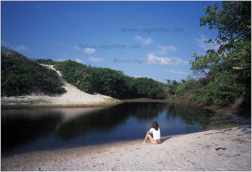 copyright: Nigel Hillier.Brazil, Para, Algodoal, woman sitting by inland pool.