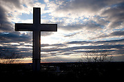 A cross is silhouetted against clouds and the setting sun.