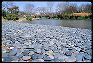 Flat granite stones line stretch of bank of Japanese Garden pond at the Missouri Botanical Garden in St. Louis, Missouri