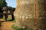 Base of the Great Tower or Tour Maitresse, with arrow slits, and a footbridge over the moat trench, at the Chateau de Guedelon, a castle built since 1997 using only medieval materials and processes, photographed in 2017, in Treigny, Yonne, Burgundy, France. The Guedelon project was begun in 1997 by Michel Guyot, owner of the nearby Chateau de Saint-Fargeau, with architect Jacques Moulin. It is an educational and scientific project with the aim of understanding medieval building techniques and the chateau should be completed in the 2020s. Picture by Manuel Cohen
