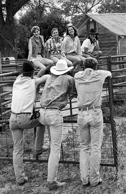 cowboys admiring girls sitting on a fence at a ranch in New Mexico