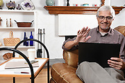Senior Man Waving On a Video Chat With Family While Under Stay at Home Restrictions