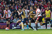 Arsenal midfielder Mesut Ozil (11) and Sunderland's Striker Jermain Defoe (18) compete for the ball during the Barclays Premier League match between Sunderland and Arsenal at the Stadium Of Light, Sunderland, England on 24 April 2016. Photo by George Ledger.