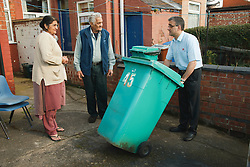 Son helping elderly south Asian parents by putting bin out.