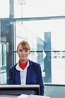 Portrait of young attractive passenger service agent standing in airport gate