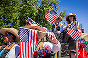 30 JUNE 2012 - PRESCOTT, AZ:  Women wave American flags at the Prescott Frontier Days Rodeo Parade. The parade is marking its 125th year. It is one of the largest 4th of July Parades in Arizona. Prescott, about 100 miles north of Phoenix, was the first territorial capital of Arizona.    PHOTO BY JACK KURTZ