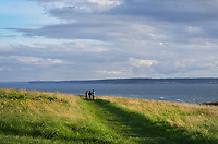 Three people viewing Admiralty Inlet from Fort Casey State Park, Washington